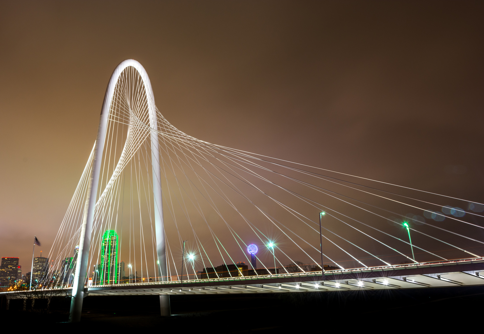 Wide view of a bridge at night in downtown Dallas with light streaks from the cars