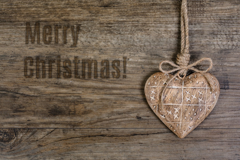 "Wooden heart decoration on vintage oak with burned caption ""Merry Christmas"""