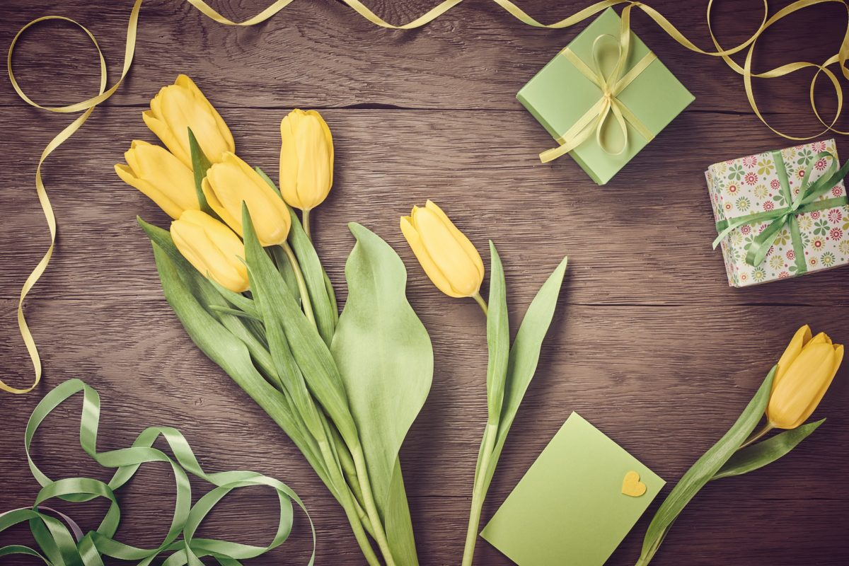 Mothers Day background. Tulips bouquet and gift boxes on wood. Beautiful spring yellow flowers, presents, note, ribbons, hearts.Still life, top view, copy space.Unusual creative holiday greeting card